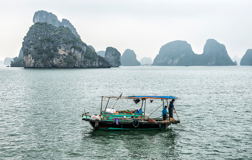 "A fisherman plies his trade from a boat in Ha Long Bay. Ha Long Bay, located on the east coast of Vietnam near Haiphong, contains over 1,900 limestone ""karst"" islands projecting from the sea, frequently shrouded in fog, mist and rain."