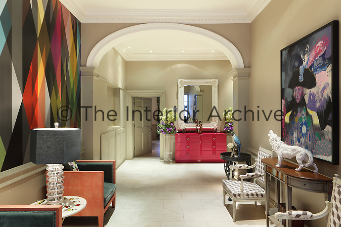 The impressive entrance hall retains the original Georgian architectural features and is a grand, classic space, which is made rich and strange by the high impact geometric wallpaper on the left wall in jewel tones. There is also a fuchsia-pink lacquered cabinet ahead of you and a pair of bespoke faux shagreen and velvet armchairs to the left.