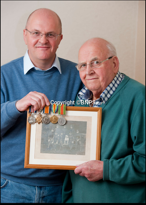 BNPS.co.uk (01202 558833)<br /> Pic: PhilYeomans/BNPS<br /> <br /> Saved by the family photos - Taylors son, William and grandson David with his medals and photograph.<br /> <br /> Saved by pictures of his loving family...<br /> <br /> An amazing tale of a heroes lucky survival through the entire First World War has been uncovered after his family revealed his remarkable tale to a local history group.<br /> <br /> Photos of loved ones that saved a soldier's life by stopping a piece of shrapnel aimed for his heart have come to light - complete with the holes the fragment left behind.<br /> <br /> Private William Taylor kept the nine pictures of his family in his wallet in his breast pocket during the entire four years of World War One.<br /> <br /> In a remarkable quirk of fate he survived a battle which left three quarters of his regiment dead or injured thanks to the stack of photos which took the impact of a shell blast.<br /> <br /> The projectile pierced the outer layer of his leather wallet and perforated eight of the nine photos.<br /> <br /> Luckily, the last picture of his younger sister Lilly stopped the fragment from going any further.