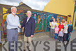 Local artist Jim Dunne with Tady Hunt, president of Athea Tidy Towns, pictured with community volunteers and a mural showing aspects of life in Athea Village, pictured here last Friday morning.