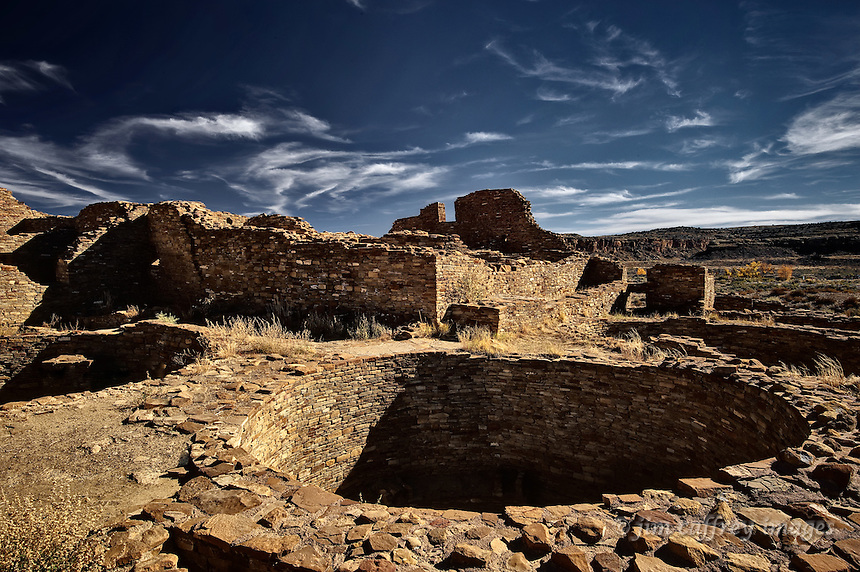 A kiva at Pueblo Bonito in Chaco Canyon National Historical Park with ruins in the background.