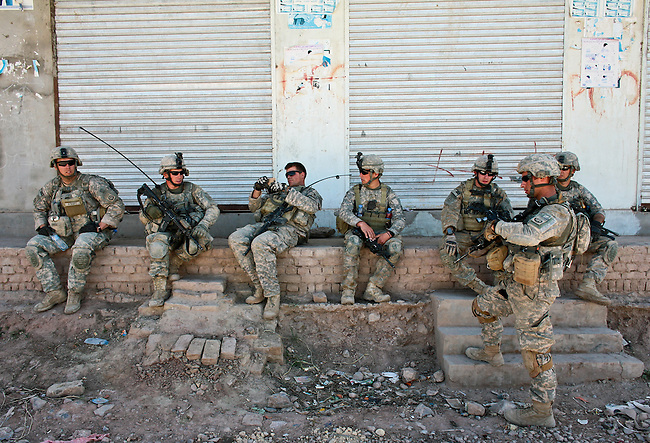 Soldiers from 2nd Battalion, 508th Parachute Infantry Regiment sit down for a brief rest outside their base after a patrol in the Arghandab valley near Kandahar, Afghanistan. March 25, 2010. DREW BROWN/STARS AND STRIPES