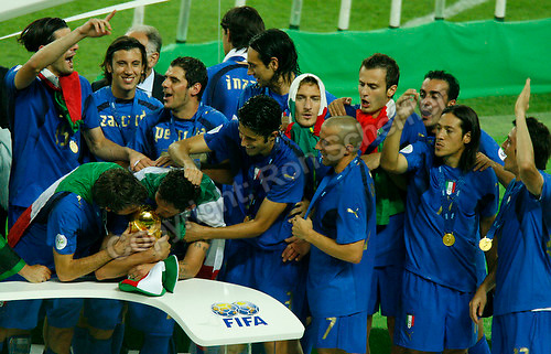 Jul 9, 2006; Berlin, GERMANY; Italy defender Andrea Barzagli, left, and defender Marco Materazzi, right, kiss the World Cup trophy while surrounded by teammates after defeating France 5-3 on penalty kicks following a 1-1 draw after extra time in the final of the 2006 FIFA World Cup at the Olympiastadion, Berlin. Mandatory Credit: Ron Scheffler-US PRESSWIRE Copyright © Ron Scheffler