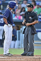 Asheville Tourists designated hitter Max White #13 talks with home plate umpire Takahito Matsuda after being ejected for drawing a line in the batters box with his bat after being called out on strikes during a game against the Kannapolis Intimidators at McCormick Field on June 7, 2014 in Asheville, North Carolina. The Tourists defeated the Intimidators 7-5. (Tony Farlow/Four Seam Images)