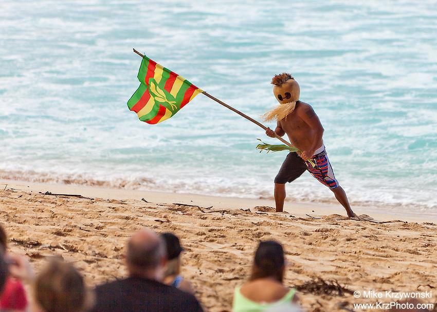 Hawaiian sovereignty movement activist wearing Hawaiin gourd warrior mask & holding Hawaii Ne flag on Sunset Beach, North Shore, Oahu, Hawaii