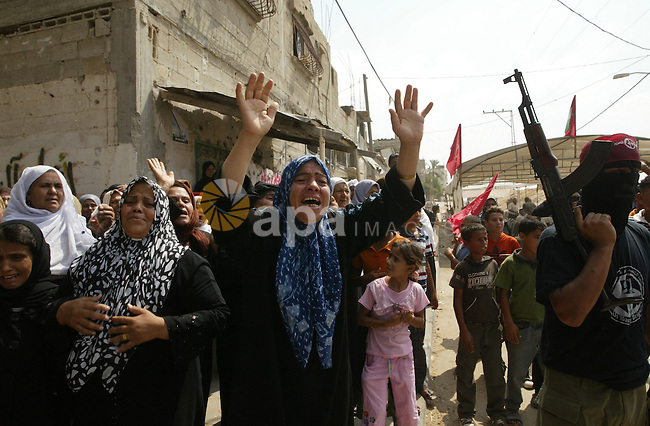 Palestinian relatives of Qassim al-Shinbari, a militant from the Popular Front for the Liberation of Palestine (PFLP), mourn during his funeral in the town of Beit Hanoun in northern Gaza Strip July 22, 2010. Israeli shellfire killed two Palestinian militants, one of them al-Shinbari, and wounded six people, including a 10-year-old girl, in the Gaza Strip on Wednesday, Palestinian medical workers and an official with a militant group said. An Israeli military spokeswoman said soldiers opened fire on militants suspected of preparing to fire a rocket at them. A security source said the troops fired a tank shell. Photo by Ashraf Amra
