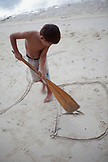 FRENCH POLYNESIA, Moorea. Dushan writing on the sand with an oar.