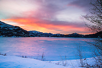 Fiery sunrise over a frozen Palisades Lake.  The warm of the sky and the cold of the ice makes for a great juxtaposition.  The late winter ice develops a sheen absent on the mid-winter snow covered ice.  The sheen reflects the fiery sky.  Palisades Reservoir is in Swan Valley Idaho