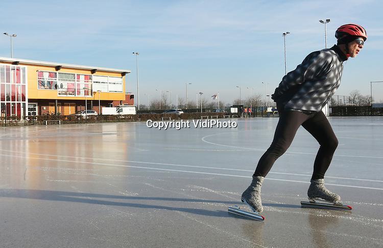 Foto: VidiPhoto<br /> <br /> ARNHEM - IJspret in Arnhem. Als eerste schaatsbaan van Nederland met natuurijs, ging Schaatsbaan De Schuytgraaf in Arnhem-Zuid maandagmorgen al open voor het publiek. Schaatsliefhebbers kregen echter nauwelijks de kans om te reageren, omdat de baan na enkele uren al weer dicht moest. Doordat de temperaturen stegen werd het ijs te zacht. Een handjevol schaatsers maakte echter van de gelegenheid gebruik om het eerste natuurijs van 2016 uit te proberen. Ook vorig jaar was De Schuytgraaf de eerste schaatsbaan in Nederland die open ging. Vrijwilligers van schaatsvereniging STG Rijnijssel waren samen met medewerkers van de gemeente Arnhem de hele nacht in de weer om een paar centimer dik ijs te construeren. De ondergrond wordt gevormd door het asfalt van de skeelerbaan. Foto: Held op sokken.