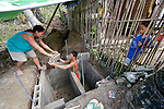 As their 4-year old son Khainer looks on, Eirene Macalalad hands a cement block to her husband Imarito as he constructs a septic tank at their home in Bacubac, a seaside neighborhood in Basey in the Philippines province of Samar that was hit hard by Typhoon Haiyan in November 2013. The storm was known locally as Yolanda. Norwegian Church Aid, a member of the ACT Alliance, is sponsoring the construction of bathrooms with septic systems for houses in the village where existing systems were destroyed by the typhoon's unusually high storm surge.