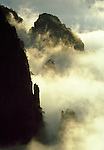 Sunrise illuminates mist clinging to the jagged slopes of China's sacred Yellow Mountain.