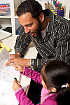 Education Preschool Headstart young male teacher working with girl pointing and talking about letters