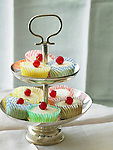 Small cheesecakes in paper cupcake cups, with red currents on top.