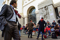 Milano, studenti e professori universitari tengono lezione in piazza Affari davanti alla borsa per protesta contro la riforma dell'istruzione. Un uomo in giacca e cravatta passa e osserva --- Milan, students and professors have class in Affari square in front of the Stock Exchange as protest against the school reform. A man with suit and tie passes by and looks