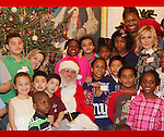 Santa Claus with Actress Amy Carlson (A/W) and founder Deborah Koenigsberger and families - Hearts of Gold links to a better life celebrates Christmas with a party #3 for mothers and their children on December 22, 2016 in New York City, New York with arts and crafts, a great turkey dinner with all the goodies and then the children met Santa Claus and had a photo with him as he gave them gifts. (Photo by Sue Coflin/Max Photos)
