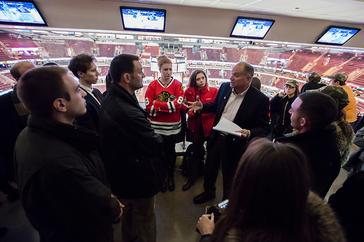 """Andy Clark, lecturer in the Driehaus College of Business, talks with his students during their class """"Behind the Scenes with Chicago Sports Organizations"""" Tuesday, Dec. 1, 2015 before a Chicago Blackhawks hockey game inside the United Center. Throughout the week-long course, students participated in behind the scenes tours of sports organizations and venues to gain first hand insights into the sports business landscape of Chicago. (DePaul University/Jeff Carrion)"""