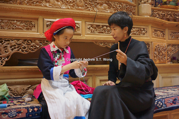 Diqing Tibetan Autonomous Prefecture, Yunnan Province, China - Tibetan women make traditional handicrafts at home, August 2018.