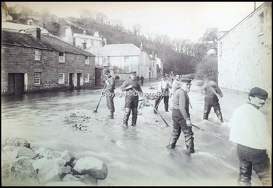 BNPS.co.uk (01202 558833)<br /> Pic: GibsonOfScilly/BNPS<br /> <br /> Flooding in Newlyn...<br /> <br /> An archive of eye-opening photographs documenting the grim reality of Poldark's Cornwall has emerged for sale for £25,000.<br /> <br /> More than 1,500 black and white images show the gritty lives lived by poverty-stricken families in late 19th and early 20th century Cornwall - around the same time that Winston Graham's famous Poldark novels were set.<br /> <br /> The collection reveals the lowly beginnings of towns like Rock, Fowey, Newquay and St Ives long before they became picture-postcard tourist hotspots.<br /> <br /> Images show young filth-covered children playing barefoot in squalid streets, impoverished families standing around outside the local tax office, and weather-beaten fishwives tending to the day's catch.<br /> <br /> The Cornish archive, comprising 1,200 original photographic prints and 300 glass negative plates, is tipped to fetch £25,000 when it goes under the hammer as one lot at Penzance Auction House.
