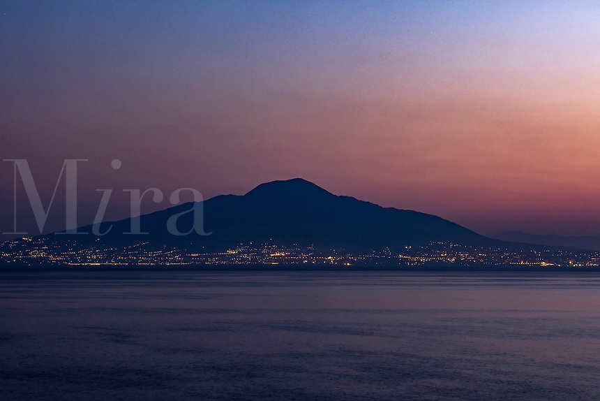 Torre del Greco at dusk with Mount Vesuvius volcano in the background, Naples, Italy