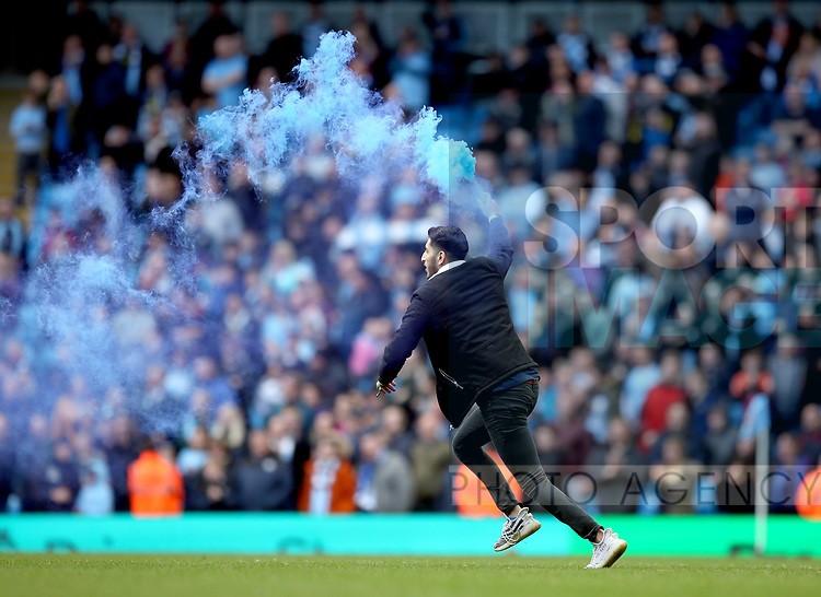 A fan runs on with a flare during the premier league match at the Etihad Stadium, Manchester. Picture date 22nd April 2018. Picture credit should read: Simon Bellis/Sportimage