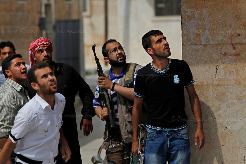 "Members of the local Free Syrian Army, along with civilians from the neighborhood look up to the sky as they attempt to predict what the Fighter Jet circling above them is going to do next. Armed with simple kalishnikovs, the Free Syrian Army can do little except watch as the aircraft turns to deliver its last bomb load before switching to its 50 caliber machine gun. ..After residents from the northern Syrian town of Al Bab organized a peaceful protest at ""Freedom Square"" (a main square renamed after the revolution began 18 months ago) a fighter jet from the Assad air force began to circle above the city. As the people scattered, a blast was heard followed by three other explosions. The fighter jet made at least 6 passes as it fired its 50 caliber  machine gun on the neighborhood below. Doctors at the local underground hospital did not allow this reporter access to the facility because of the load of patients coming in. Unconfirmed reports by the FSA spokesperson in Kilis say that 7 people died and 50 were injured. ..Photo: Javier Manzano / August 31, 2012"