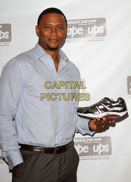DAVID RAMSEY.Visits Gifitng Services held Gifting Services Showroom, West Hollywood, CA, USA..August 23rd, 2010.half length blue shirt hand in pocket holding sneaker trainer .CAP/ADM/FS.©Faye Sadou/AdMedia/Capital Pictures.