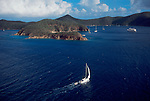 "British Virgin Islands, Aerial image, Norman Island (the original ""Treasure Island"" in Robert Louis Stevenson's ""Kidnapped""), Caribbean Sea, sailboat approaching the Bight anchorage"
