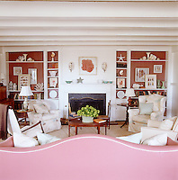 A view from behind a pink sofa to the fire place and book shelves, highlighted by the painted brick colour.
