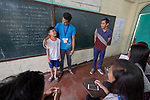 "Larren Jo ""LJ"" Bacilio (right), a teacher in the Alternative Learning System of the Kapatiran-Kaunlaran Foundation (KKFI), watches as students act out a lesson during a class in the Tondo neighborhood of Manila, Philippines. <br /> <br /> KKFI is supported by United Methodist Women."