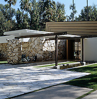 The modern geometric lines of the roof contrast with the rough stone walls of the house
