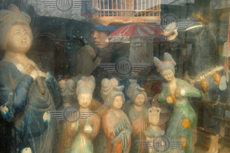 Figurines of women in traditional dress are displayed in the window of an antiques store near Hou Hai Lake.