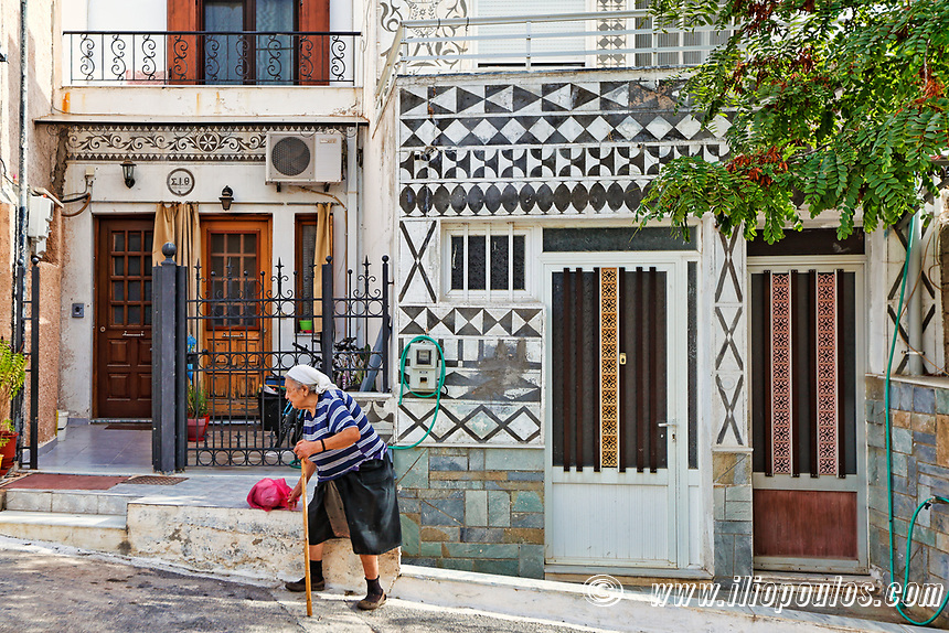 Old woman outside traditional houses decorated with the famous geometric scratch patterns in the medieval mastic village of Pyrgi on the island of Chios, Greece