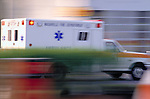 blurred ambulance speeding to emergency
