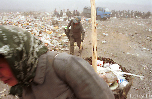 Migrants work on a garbage dump in Beijing, the Chinese capital...Between 50-100 Chinese from a small village in southwestern China's Sichuan province live and work here, one thousand miles away from home. They are part of a cooperative selling scraps and wastes to local farmers and factories...They look for bits of wire, bottles and plastics that they can re-sell. They earn about 300 yuan (US$36) a month per person, which is low by urban standards but is about 10 times as much as wages at home in Sichuan....Picture taken March 1999.Copyright Justin Jin