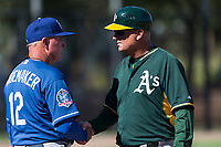 Los Angeles Dodgers coach John Shoemaker (12) talks to Oakland Athletics coach Steve Scarsone during an Instructional League game against the Oakland Athletics at Camelback Ranch on September 27, 2018 in Glendale, Arizona. (Zachary Lucy/Four Seam Images)