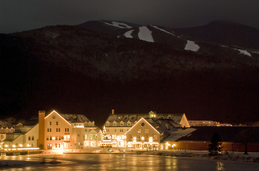 Waterville Valley Town Square, aglow with holiday lights, nestled at the foot of Mt. Tecumseh in New Hampshire's White Mountains.