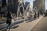 """Visitors to Flatiron Plaza in New York on Monday, November 28, 2016 interact with """"Flatiron Sky-Line"""" created by architectural firm LOT. The Christmas installation is the centerpiece of the Flatiron 23rd Street Partnership's  holiday programming. The ten illuminated arches with hammocks suspended underneath engage visitors to relax and to contemplate the architectural wonders of the neighborhood, specifically the Flatiron Building. (© Richard B. Levine)"""