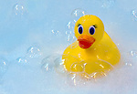A yellow rubber duck floats in a bubble bath.