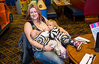 A mother tandem feeds her two children, one about one about twelve weeks and one about 28 months old, at a sling meet held in the family restaurant and play area in a pub.