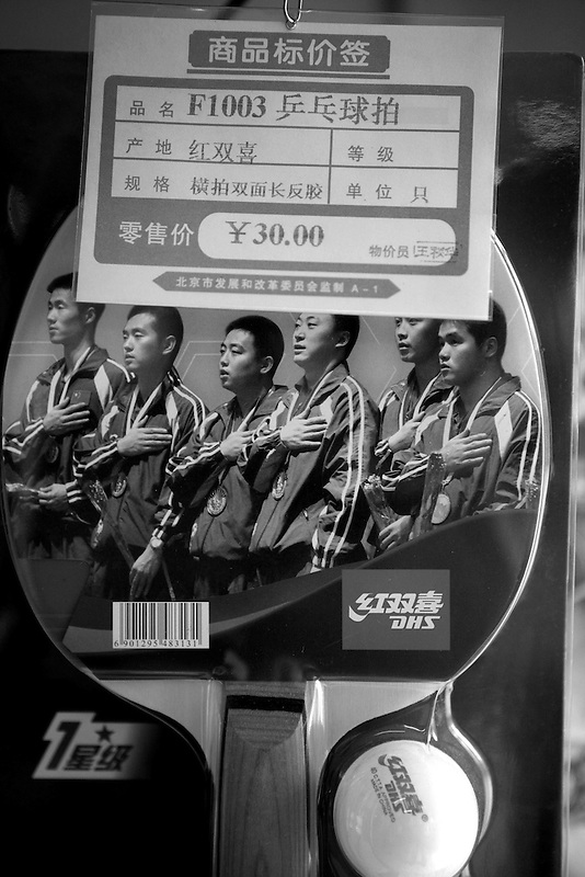 A table tennis paddle featuring a photograph of the Chinese National team for sale in a shop specializing in table tennis gear in Beijing.