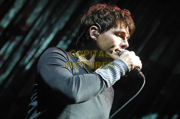 MORTEN HARKET.AHA Live at Nottingham Arena, Nottingham..UK, United Kingdom..9th December 2005.Ref: JEZ.half length performing live onstage on stage singing microphone music gig concert show pendant chain necklace jewellery earpiece earphone.www.capitalpictures.com.sales@capitalpictures.com.©Capital Pictures