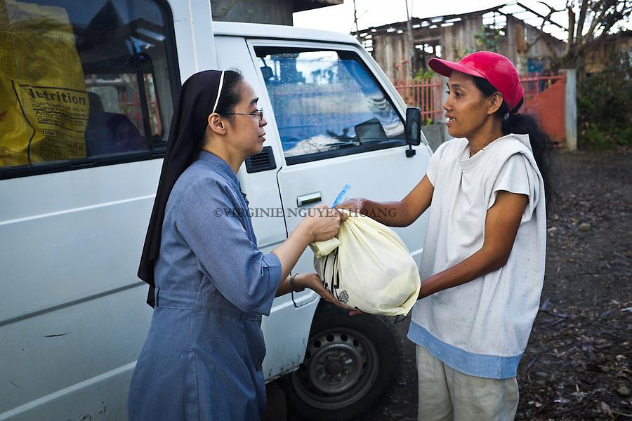 Sister Gertrude giving a bag of reliefs at one of the inhabitant of the village of Palo. <br /> <br /> Soeur Gertrude donner un sac de secours &agrave; l'une des habitantes du village de Palo.