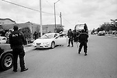 Culiacan, Sinaloa.Mexico.July 6, 2008..Dozens of armed State policeman, along with the Mexican military, patrol the city streets in a show of force in Culiacan. They set up road-blocks and travel through the poorer burrios. From January 1 to mid-July 2008 there have been 535 drug related killings in Sinolao, many of them were police officers...At one point they surround a house with gunmen as they had a tip that there were drugs in a private home..