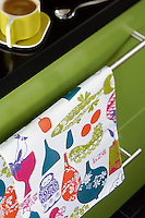 A bright yellow coffee cup and saucer and multi-coloured tea towel against the vibrant green of the kitchen units