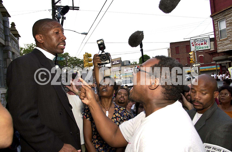 A protestor, right, yells at a local minister, after hundreds turned out at a protest of the July 12 beating of Thomas Jones by city police officers attempting to arrest the carjacking suspect, when he was denied access, along with others, becasue of lack of space in the church Sunday, July 23, 2000, in Philadelphia. The beating incident was videotaped by a local television station helicopter, and broadcast around the world, shedding a bad light on the city of Philadelphia two weeks before the Republican National Convention. (Photo by William Thomas Cain/Newsmakers)