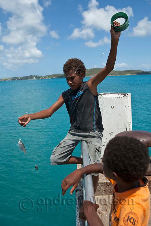 Torres Strait Islander kids fishing off the jetty at Horn Island, Torres Strait Islands, Queensland, Australia