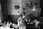 Older woman in her living room Peabody Estate flat tenement building Tower Hamlets east London UK 1975 <br />