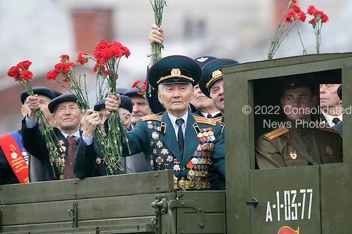 Veterans of Russia's military hold up flowers as they ride during a military procession commemorating the 60th anniversary of the end of World War II in Red Square, Moscow, Russia, Monday, May 9, 2005. <br /> Credit: Eric Draper - White House via CNP