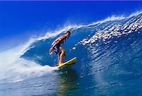 A surfer rides a beautiful blue wave at Pupukea beach, North shore Oahu.