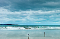 Waves, tide  and surfers with surfboards at Lahinch, Lehinch,  famous surfing beach, County Clare, West Coast of Ireland